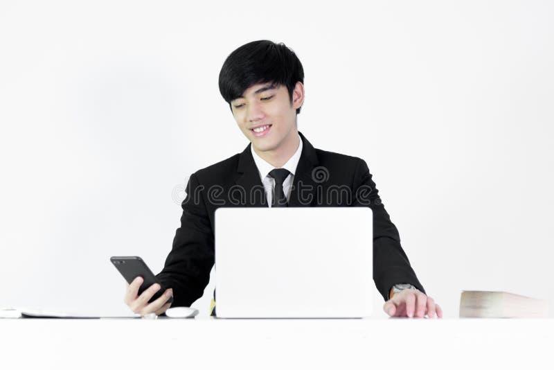 坐在书桌和使用与电话的亚洲经理商人,被隔绝在白色背景 免版税库存图片