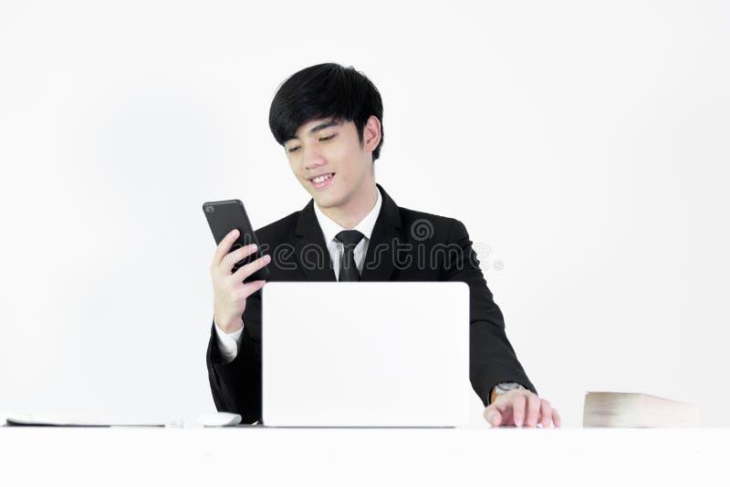 坐在书桌和使用与电话的亚洲经理商人 免版税库存图片