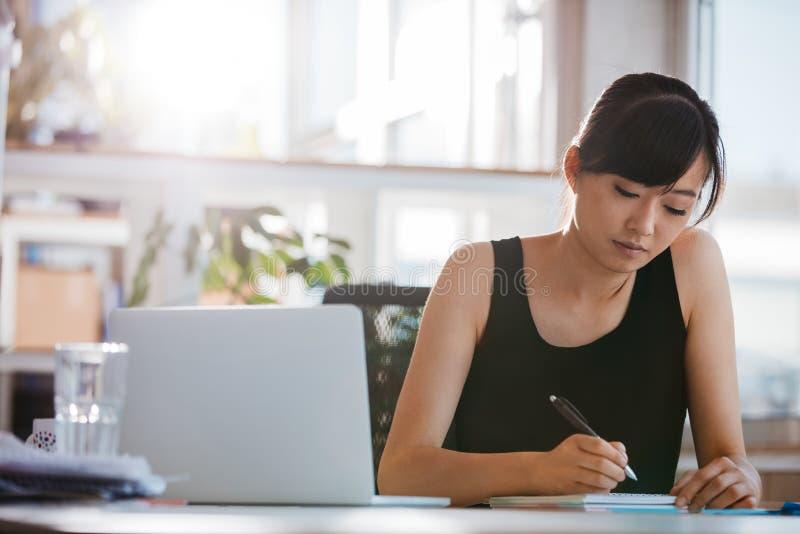 坐在书桌和写笔记的少妇 免版税库存照片