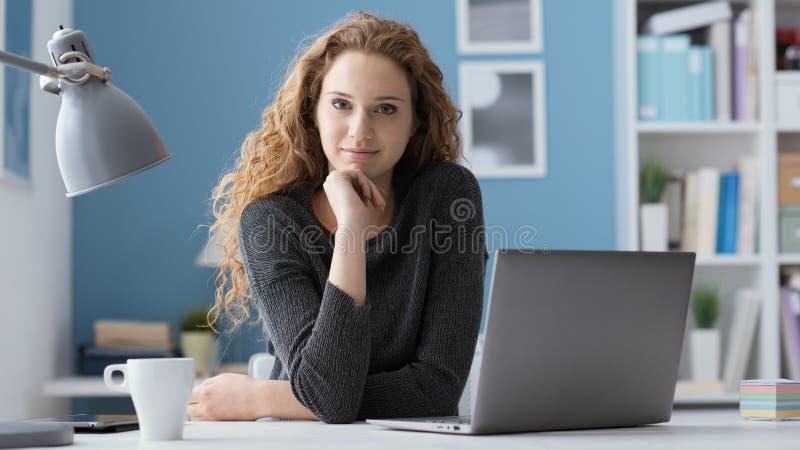 坐在书桌和摆在的年轻女人 库存照片