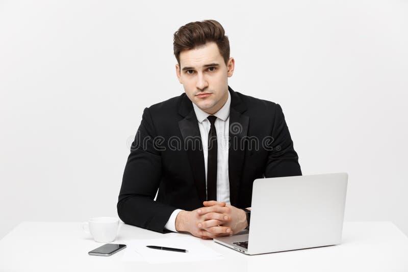 坐在书桌和看照相机的确信的经理画象 E 免版税库存照片
