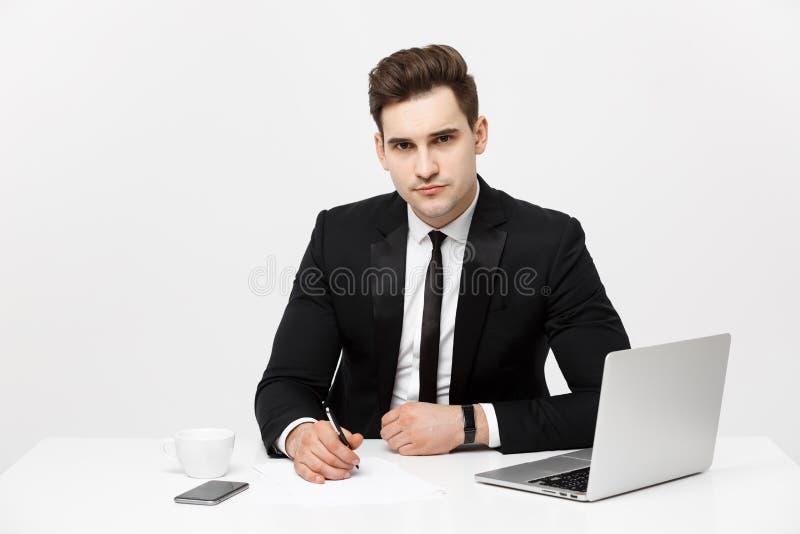 坐在书桌和看照相机的确信的经理画象 E 库存图片