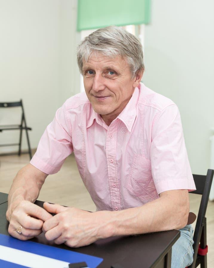 坐在书桌和看照相机,桃红色衬衣的更老的人 免版税库存图片