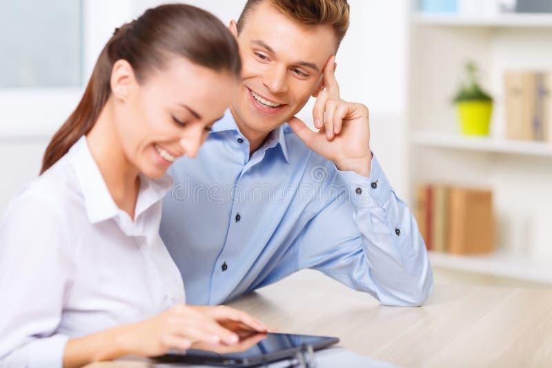 坐在书桌和笑的办公室夫妇 免版税库存照片