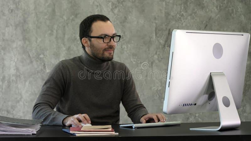 坐在书桌在办公室和woking在计算机的商人 免版税库存照片