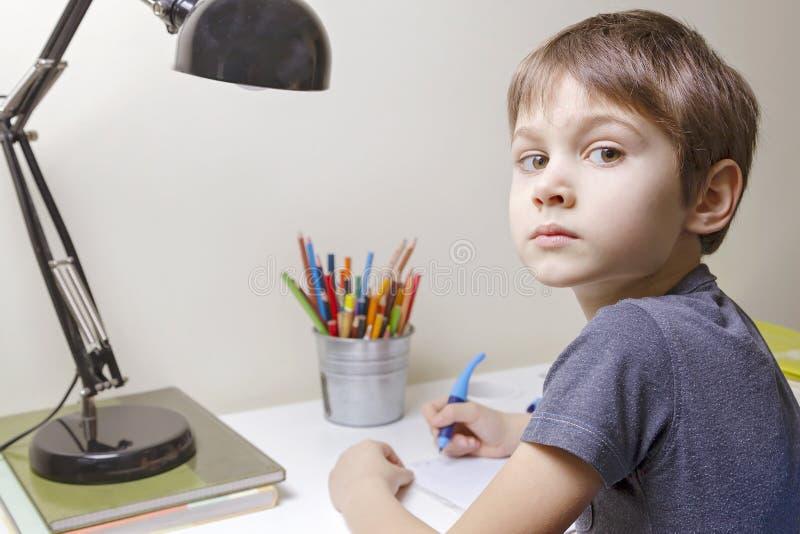 坐在书桌家和做他的家庭作业的男孩 儿童文字 学校,孩子,教育概念 免版税库存图片
