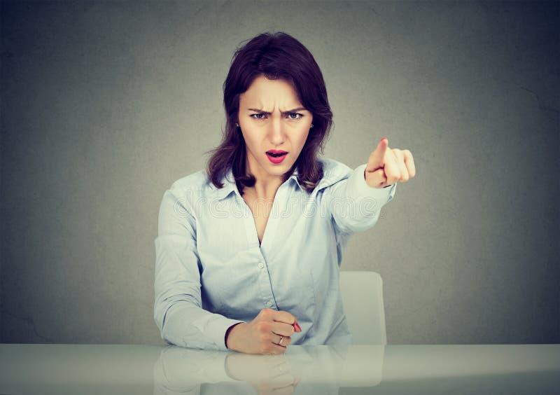 坐在书桌尖叫的指向的恼怒的女商人与手指出去 免版税图库摄影