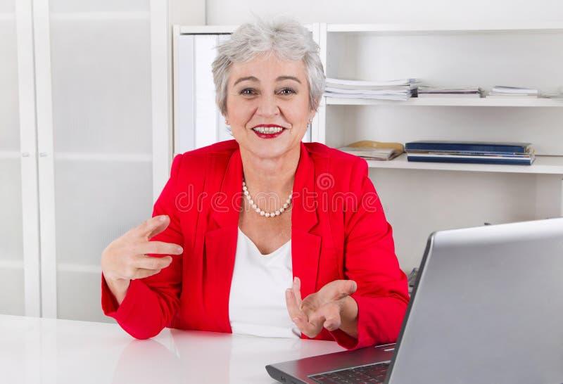坐在书桌我们的可爱的更老的微笑的资深女实业家 免版税图库摄影
