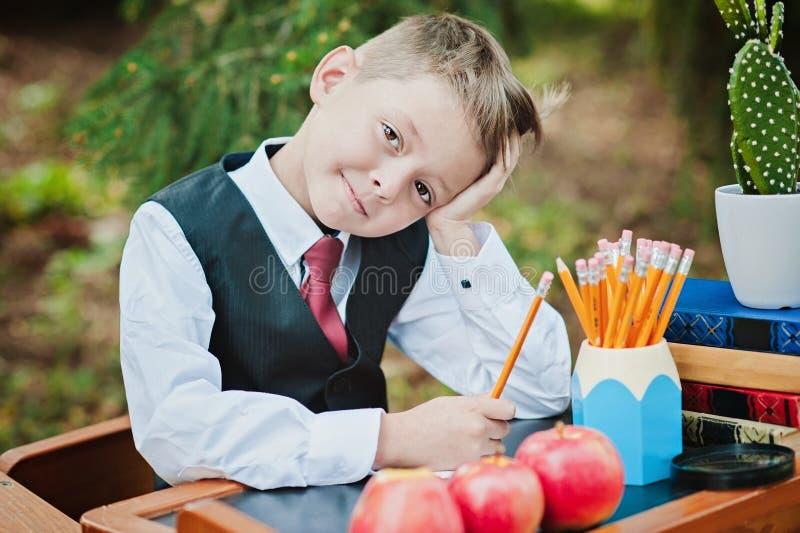 坐在书桌的一个渴望的一年级学生男孩的画象 免版税图库摄影