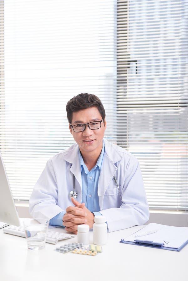 坐在书桌的一位微笑的确信的男性医生的画象在医疗办公室 免版税图库摄影