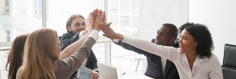 坐在书桌的不同的买卖人庆祝给高五的成功 免版税库存照片