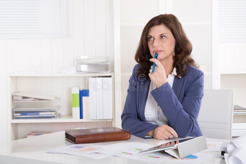 坐在书桌的不快乐的更老的沉思女商人 免版税库存照片