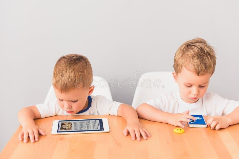 坐在书桌的两个liitle男孩在演播室 库存图片
