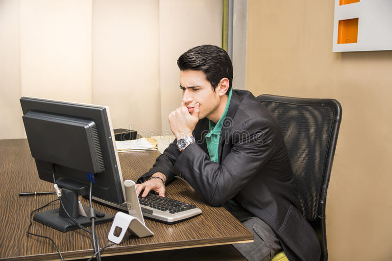 坐在书桌的严肃的年轻商人在办公室 库存照片
