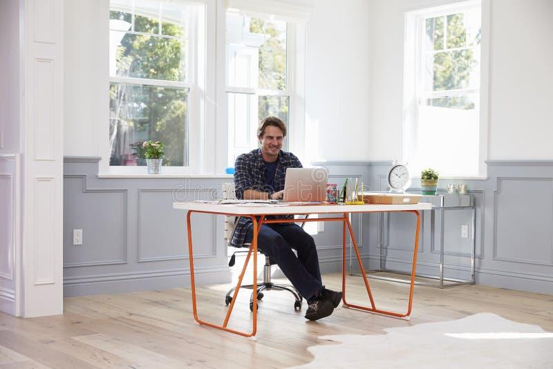 坐在书桌的人运转在内政部的膝上型计算机 库存照片