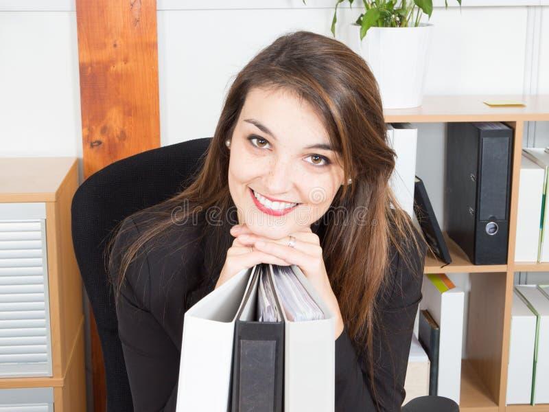 坐在书桌的办公室少妇倾斜在横渡的手,当微笑时 免版税库存图片