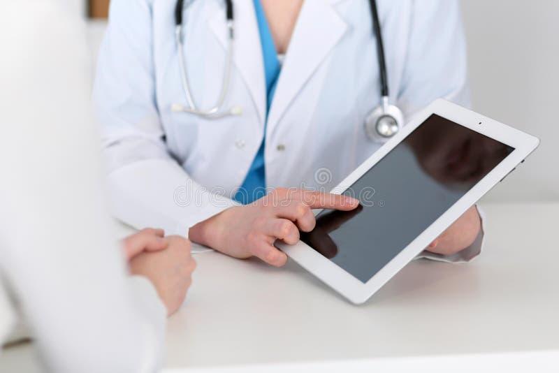 坐在书桌的医生和患者的特写镜头 指向入片剂个人计算机的医师 医学和健康加州 库存照片