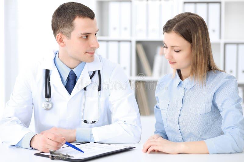 坐在书桌的医生和患者 医学和医疗保健概念 免版税图库摄影