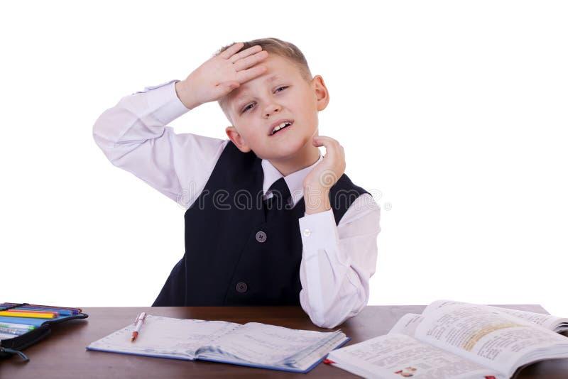 坐在书桌的十年高中学生 免版税库存图片