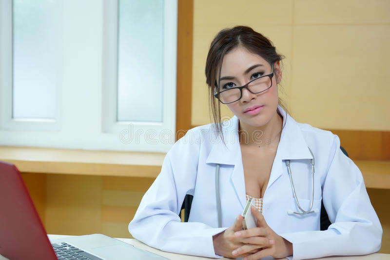 坐在书桌的可爱的年轻女性医生在办公室 免版税库存图片