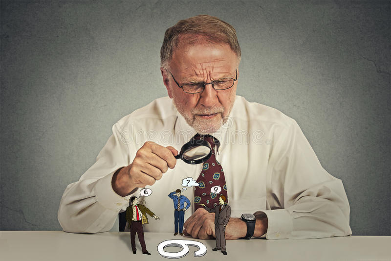 坐在书桌的商人怀疑地看小组争论人 免版税库存照片