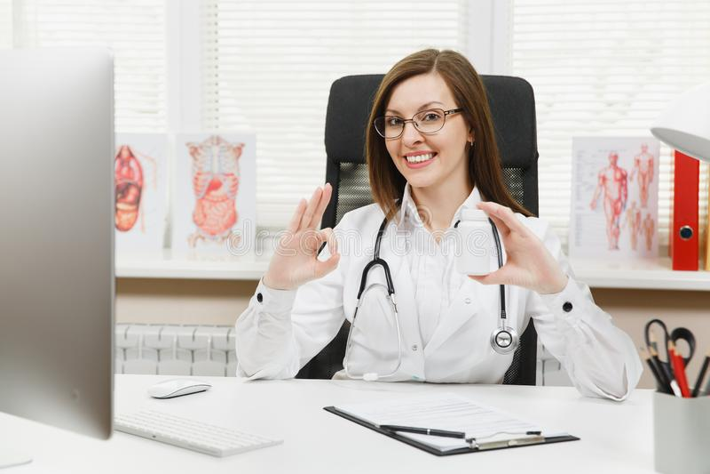 坐在书桌的女性医生,拿着有白色药片的瓶,与医疗文件一起使用在轻的办公室 免版税库存图片