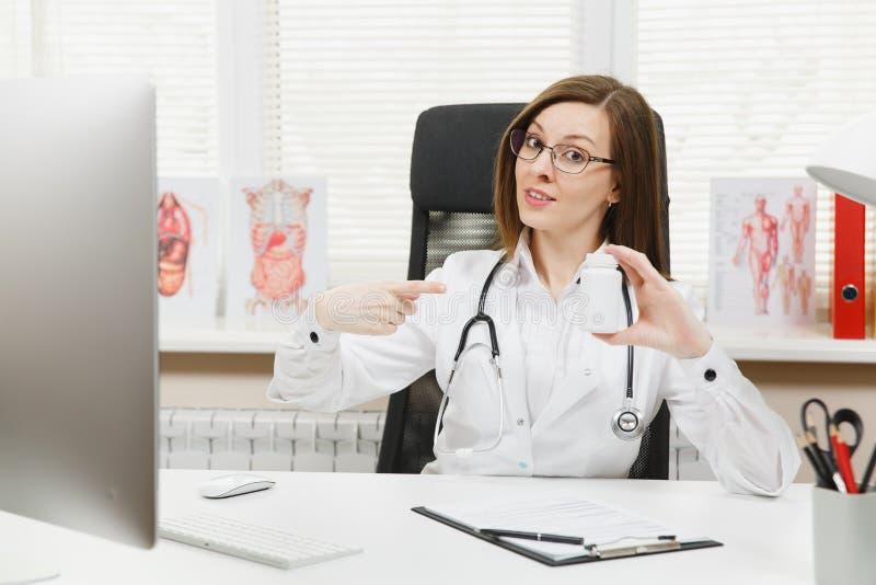 坐在书桌的女性医生,拿着有白色药片的瓶,与医疗文件一起使用在轻的办公室 免版税库存照片