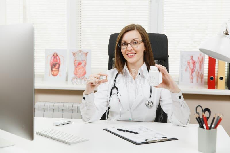 坐在书桌的女性医生,拿着有白色药片的瓶,与医疗文件一起使用在轻的办公室 免版税图库摄影