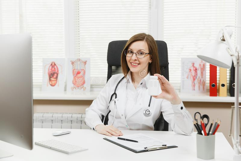 坐在书桌的女性医生,拿着有白色药片的瓶,与医疗文件一起使用在轻的办公室 库存照片