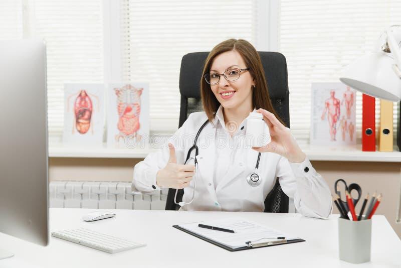 坐在书桌的女性医生,拿着有白色药片的瓶,与医疗文件一起使用在轻的办公室 库存图片