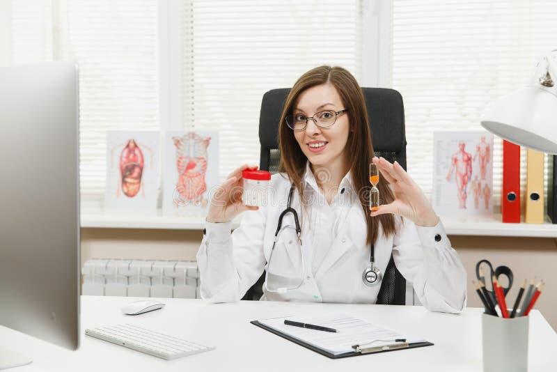 坐在书桌的女性医生,拿着有白色药片的瓶,滴漏,与在光的医疗文件一起使用 免版税图库摄影