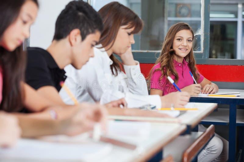 坐在书桌的少年女小学生 库存图片