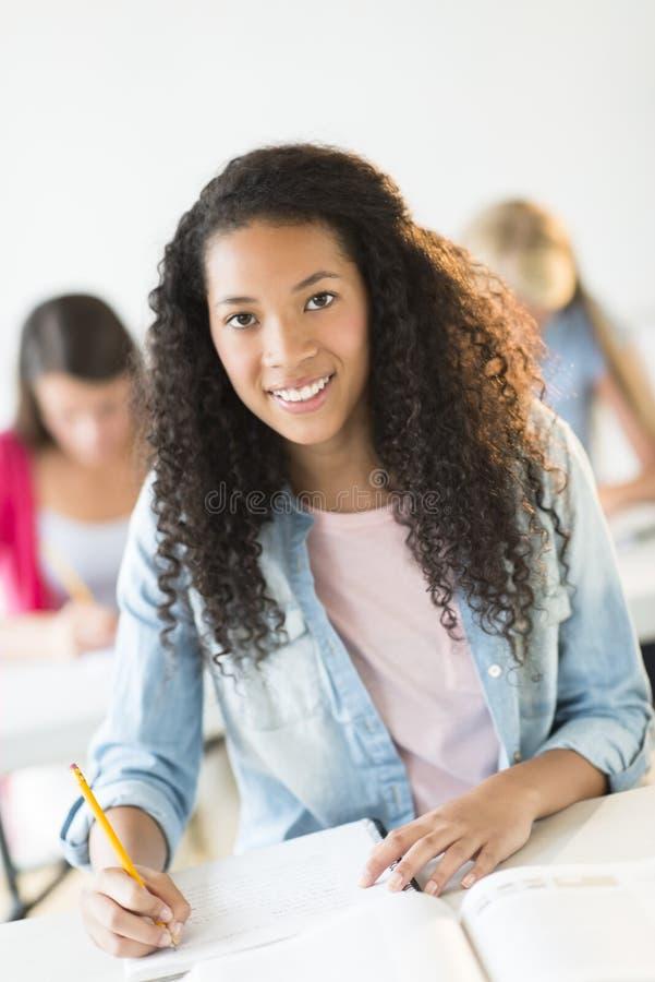 坐在书桌的少年学生在教室 库存图片