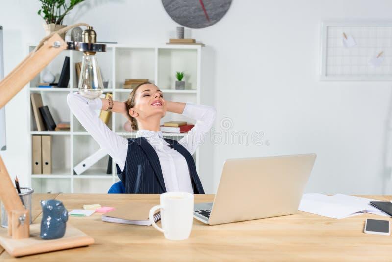 坐在书桌的年轻女实业家在办公室用手 免版税库存照片