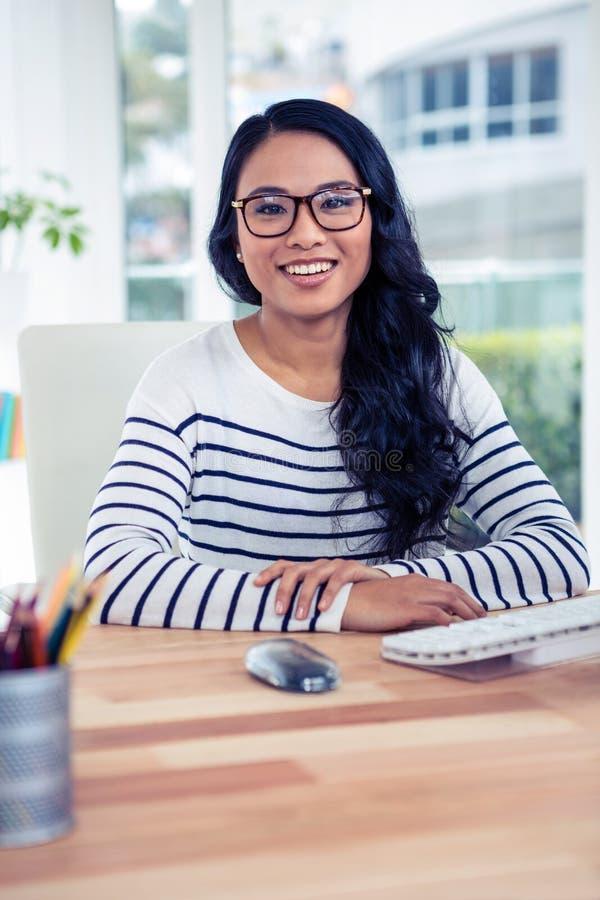 坐在书桌的微笑的亚裔妇女摆在为照相机 库存图片