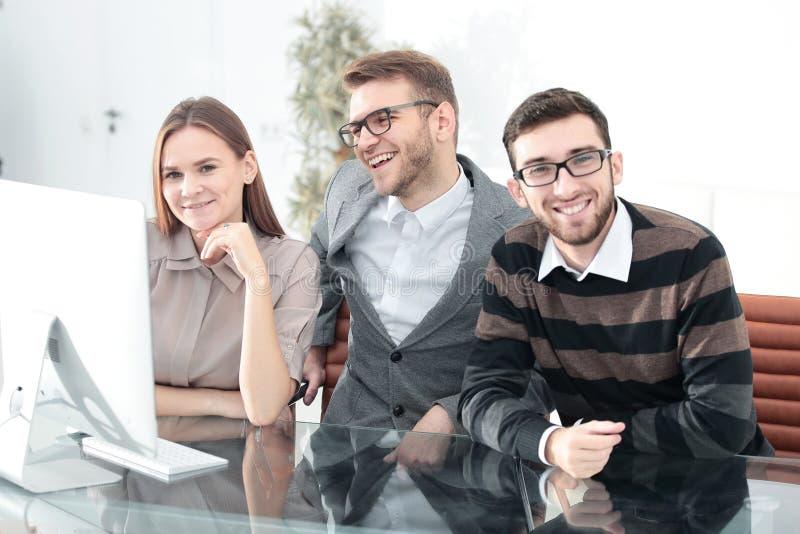 坐在书桌的微笑的企业队 库存照片