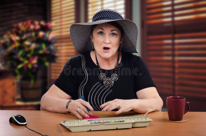 坐在书桌的恶心的成熟妇女 免版税库存图片