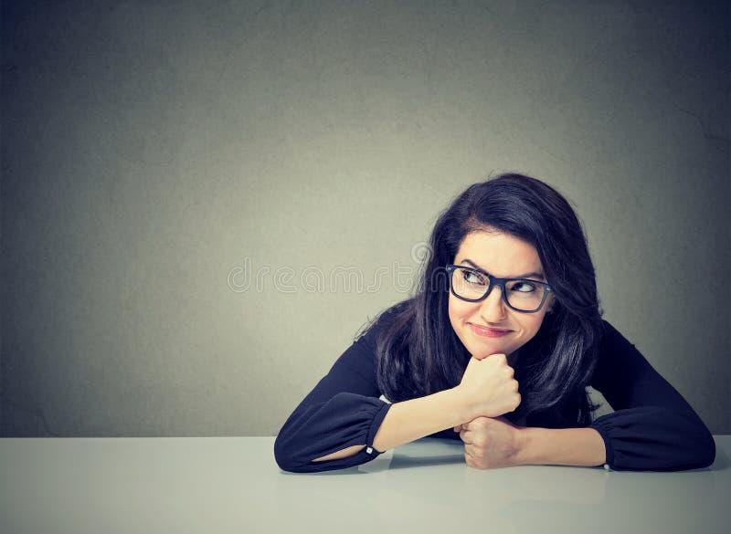 坐在书桌的想法的女商人 库存照片