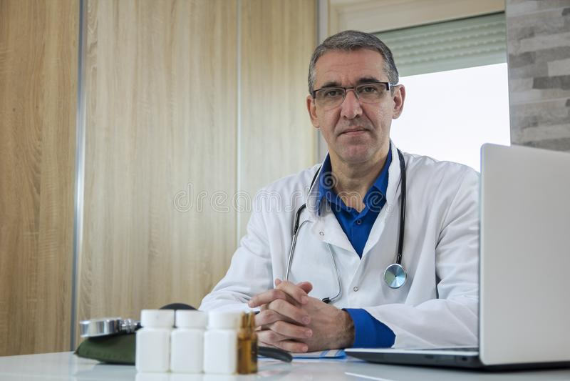 坐在书桌的成熟男性医生在医生` s室 库存照片