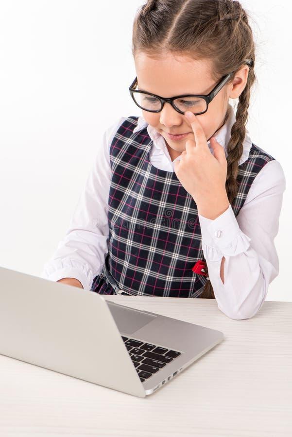 坐在书桌的玻璃的女小学生 免版税库存照片