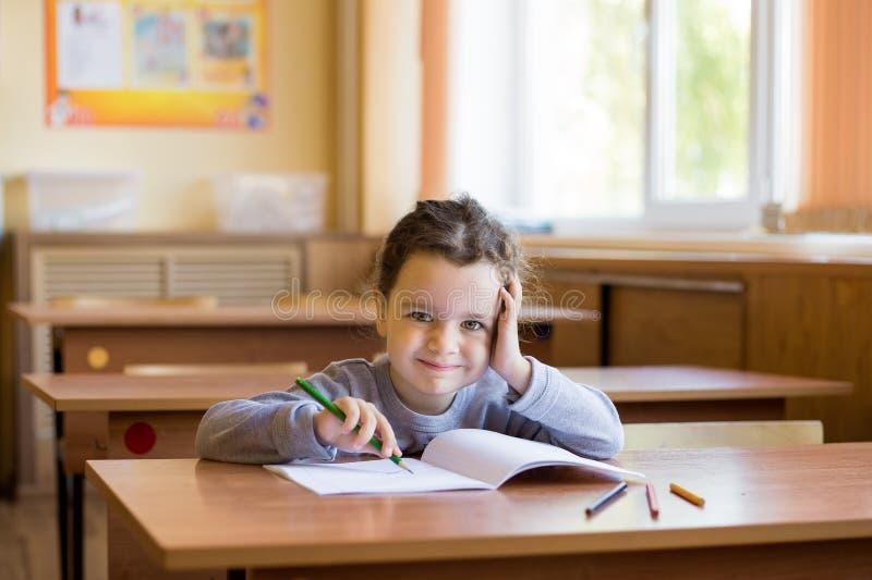 坐在书桌的白种人矮小的微笑的女孩在教室和在一个纯净的笔记本开始画 免版税库存照片