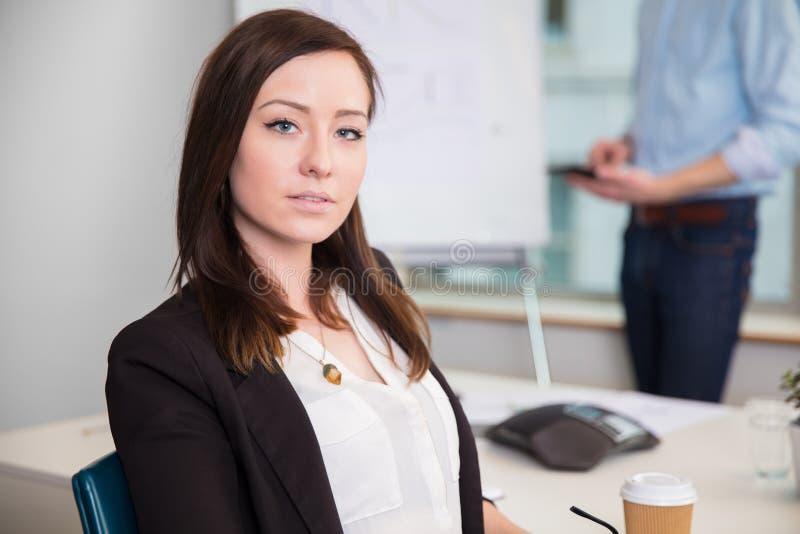 坐在书桌的确信的女实业家在办公室 库存照片