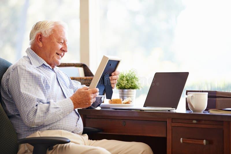 坐在书桌的老人看照片框架 免版税库存照片
