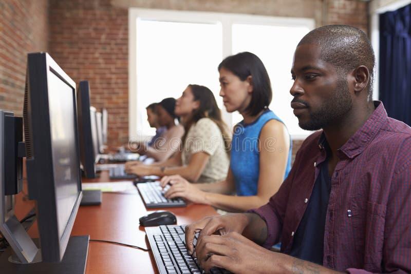 坐在书桌的职员使用计算机在繁忙的办公室 图库摄影