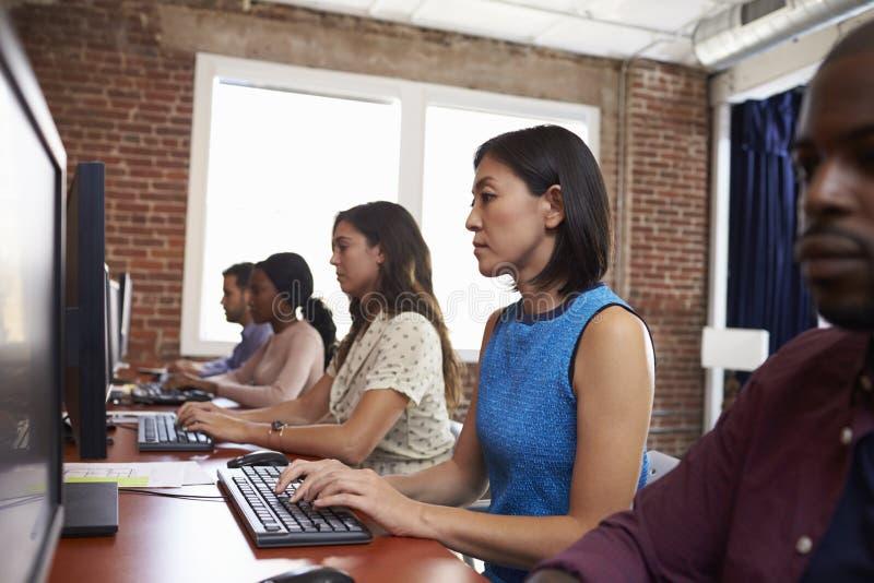 坐在书桌的职员使用计算机在繁忙的办公室 免版税图库摄影
