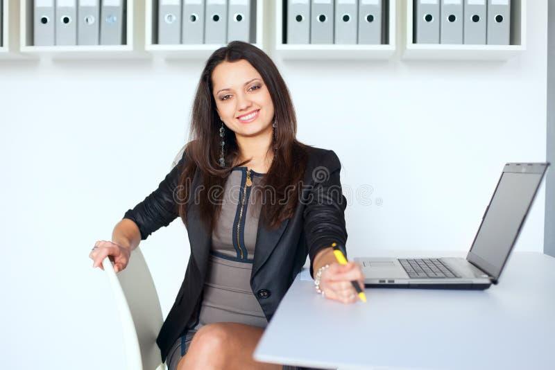 坐在书桌的年轻微笑的女商人 免版税图库摄影