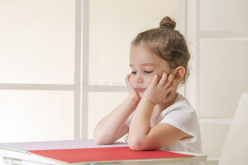 坐在书桌等待的传神小女孩 图库摄影