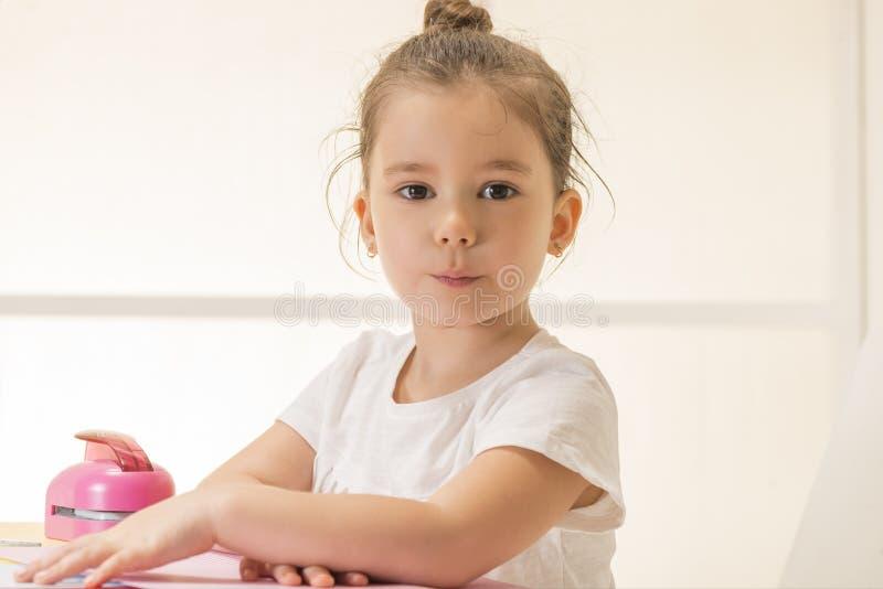 坐在书桌等待的传神小女孩 免版税库存照片