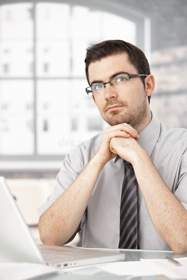 坐在书桌认为的年轻男性画象 免版税库存照片
