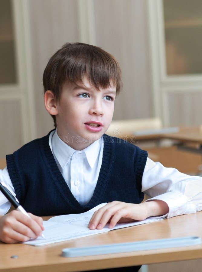 坐在书桌,教室的努力学生 库存照片